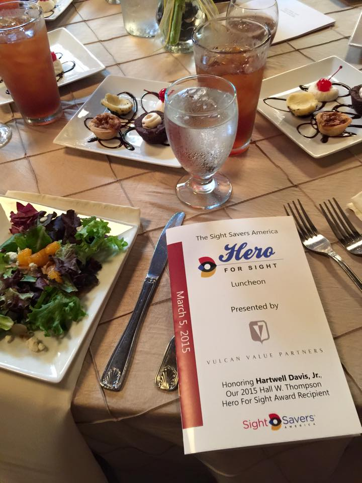 Photo of table with food, drinks, deserts, and brochure for hero for sight luncheon.