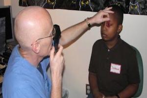 man screening child's eyes